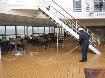 Crew member shoveling snow on pool deck.