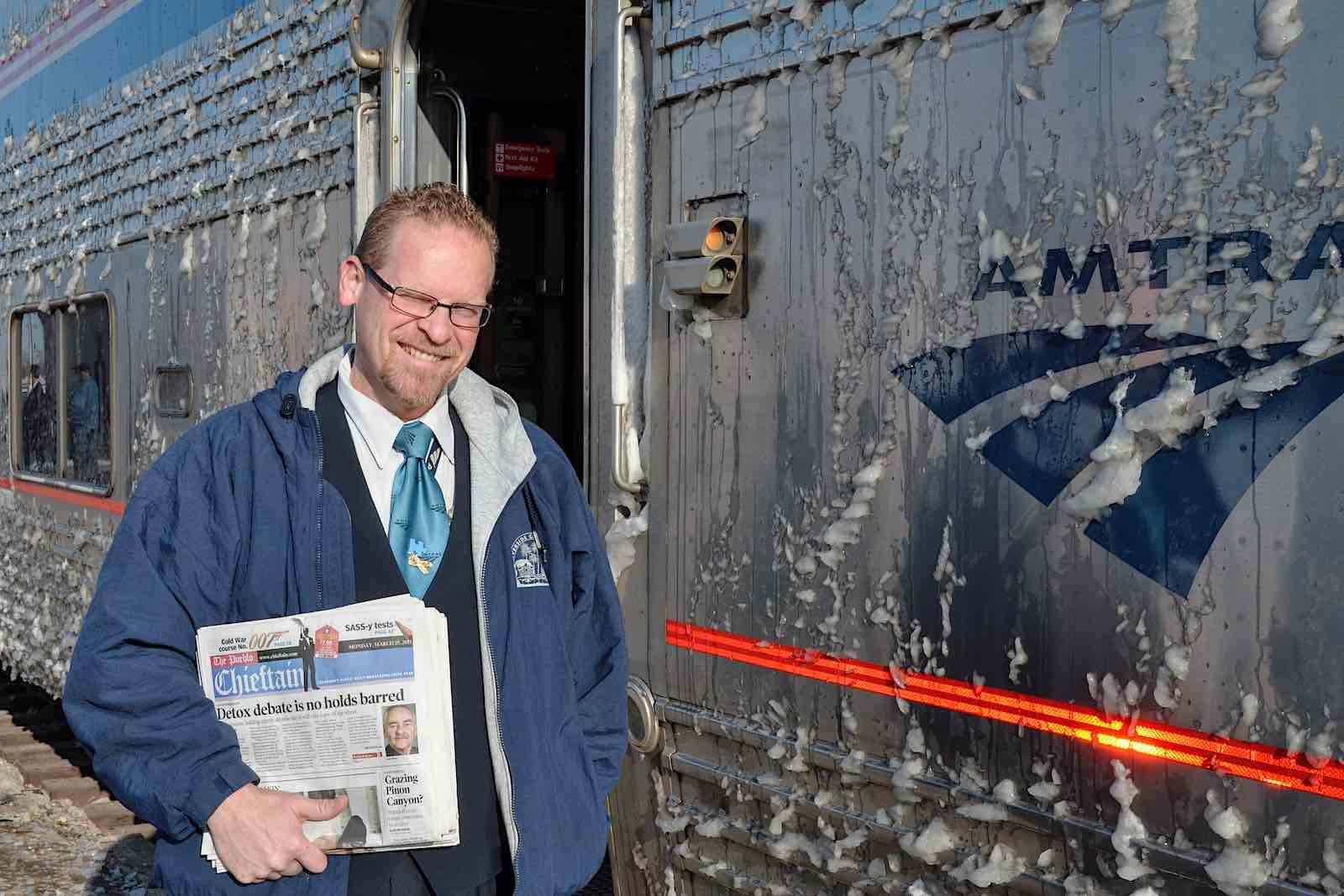 amtrak attendant holding morning newspapers