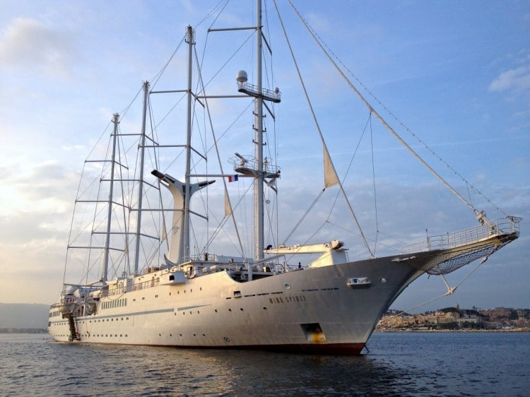 At sunset, the Windstar Wind Spirit is about to raise the anchor to depart the port of Cannes.