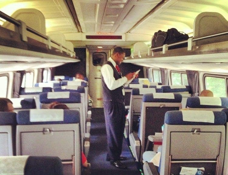 Amtrak coach attendant, Joseph, asks coach passengers for dinner reservation requests aboard the Palmetto.