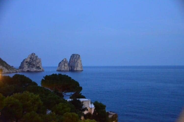 The Faraglioni rock formations off the coast of romantic Capri tower more than 300-feet above the sea, on a Mediterranean cruise.