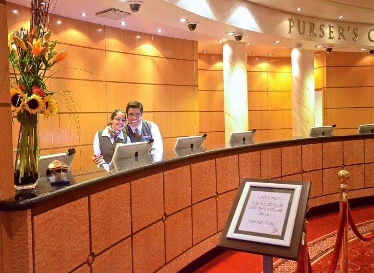 Saying hi to the front desk staff, here it's Cunard Queen Mary 2, is one of my 12 cruise hacks for women cruising solo
