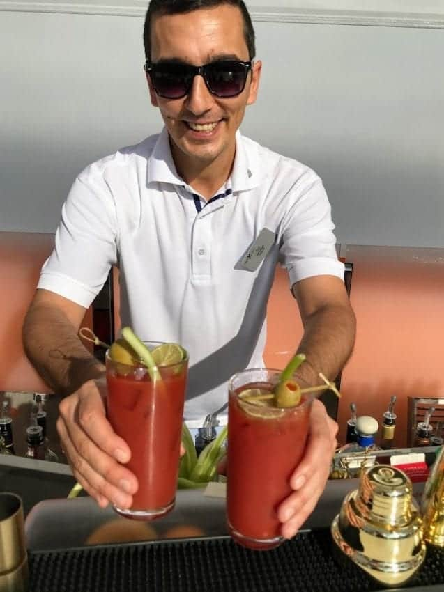 Bartender aboard Celebrity Edge making Bloody Mary cocktails.