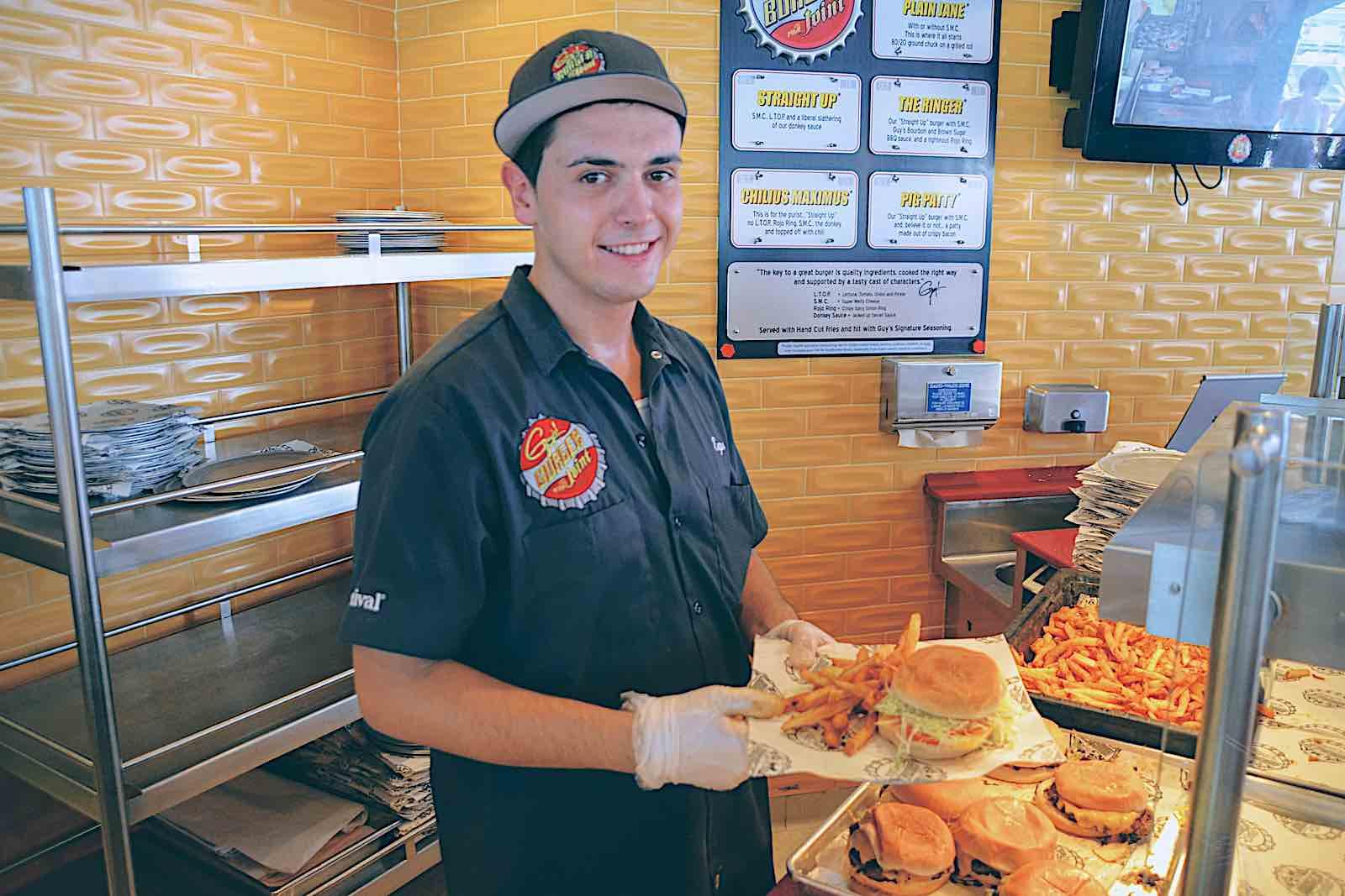Guy's Burger Joint Line Cook in Uniform serves a Guy Fieri burger.